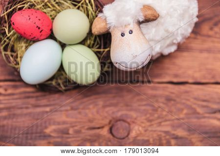 cute toy sheep near easter eggs basket with copy space bellow on old wood basket