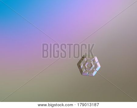 Macro photo of real snowflake: small and simple snow crystal of hexagonal plate type with amazing pattern of six heart-shape elements around central hexagon. Snowflake glittering on bright blue - pink - brown gradient background in cold light.