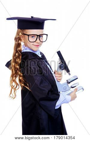 Portrait of a cute nine year old girl in an academic gown and hat holding a microscope. Educational concept. Isolated over white.