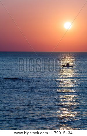 Scenic view of colorful ocean sunset with small fishing boat silhouetted in foreground.