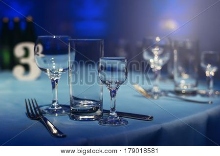 Table setting empty wine glasses piles. Banquet room in a blue haze. Wedding decoration of the hall. Twilight and blue lighting lamps and candles. White tablecloth. Laying