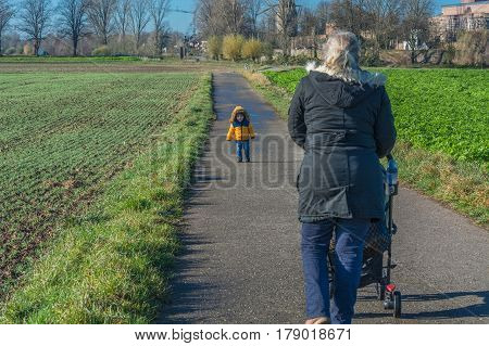 Grandmother with grandson while walking and pushes a baby carriage.