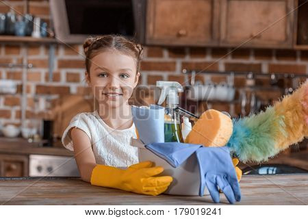 Adorable Little Girl With Cleaning Supplies Looking At Camera At Home