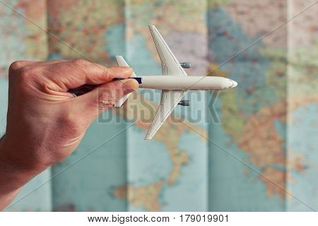 airplane model in hand on the world map