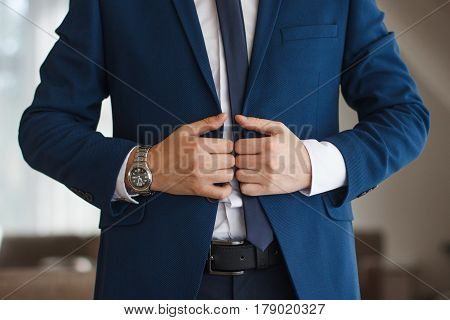 Man straighten his tie over bright shirt close up.