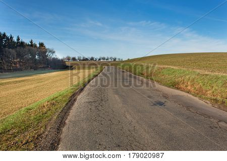 Old rural asphalt road in the Czech Republic. Granite road bollard. Agricultural landscape
