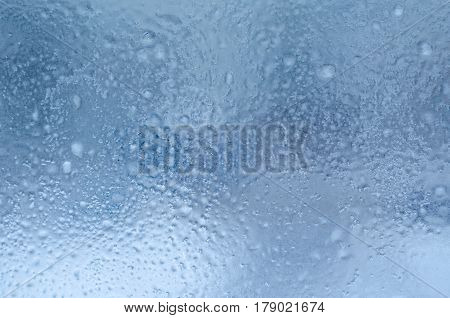 Rain drops and frozen water on window glass background