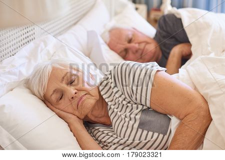 Senior woman sleeping soundly while lying in bed in the morning with her husband asleep behind her