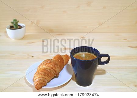 One Cup of Coffee and a Plate of Butter Croissant served on the Wooden Table with a Cute Mini Cactus Plants