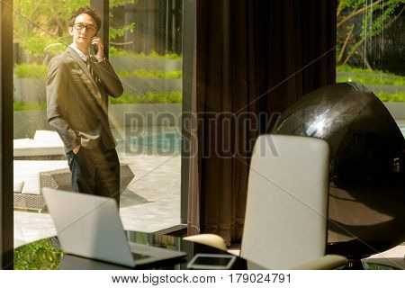 Asian smart business man calling on the smarphone in his office.