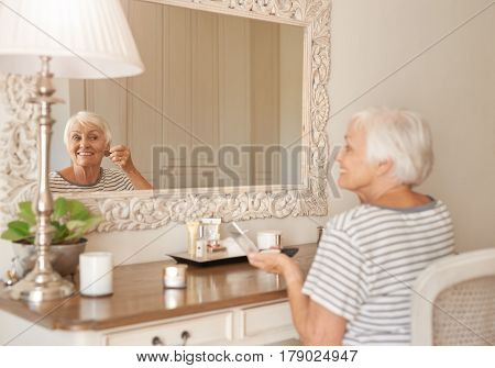 Smiling senior woman applying foundation to her cheek with a makeup brush while sitting alone in front of a mirror in her bedroom at home