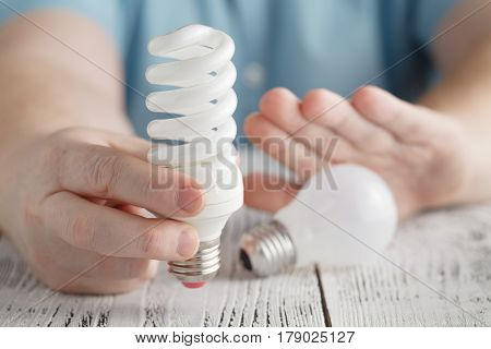 Man Holding An Energy Saving Lamp And Refuse  Normal Light Bulb