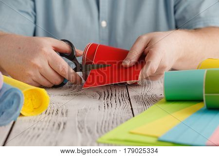 Male Cut Red Color Paper On Wooden Table