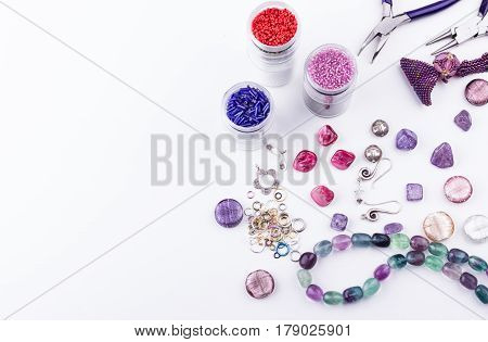 Beads and stones on white background. Top view.