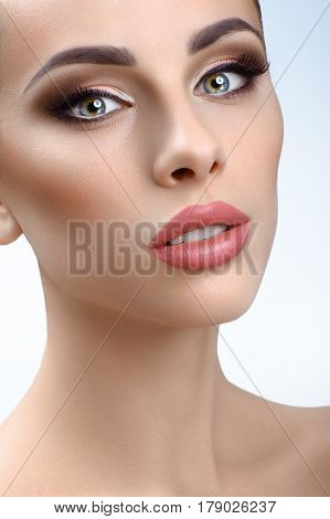 Face of youth. Vertical cropped close up of a gorgeous young woman with perfect skin wearing professional makeup with brown smoky eyes and pink lipstick cosmetics skincare beauty salon face concept