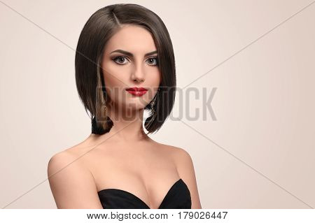 Young grace. Elegant young woman in a black dress smiling softly to the camera posing in a black dress on beige background copyspace skincare cosmetology hair therapy treatment salon fashion concept