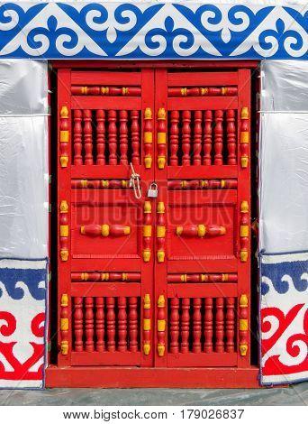 Red wooden door of Kazakh house (the yurt)