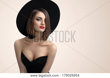 Horizontal portrait of a gorgeous sexy young woman posing seductively wearing black dress copyspace seduction sexuality hot body breasts corset femininity style fashion elegance concept poster
