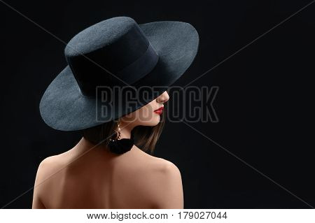 Rearview studio shot of a mysterious woman in a hat on black background red lips makeup cosmetics beauty fashion style elegance concept