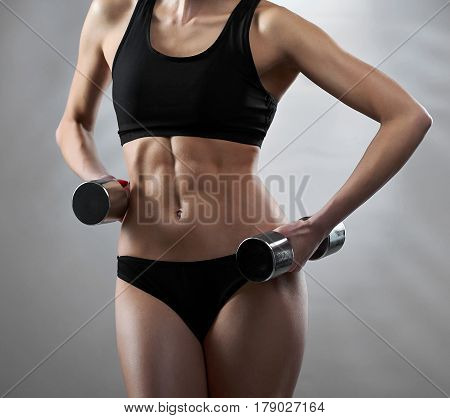 Determination master. Cropped shot of a stunning hot sexy body of a young fitness woman posing with dumbbells in her hands on grey background