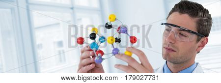Scientist experimenting molecule structure against digital composite image of glass window