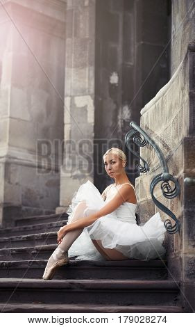 Looking unprotected. Young attractive ballet dancer sitting on the stairs embracing her knees soft focus