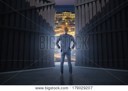 Wear view of businessman with hands on hip against illuminated buildings in city 3d