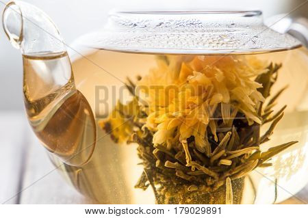 closeup of a glass tea pot with Flower Chinese tea on light wooden background