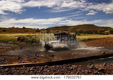 SUV during the safari in South Africa. spray of water, terracotta road, blue sky, white clouds, horizon line