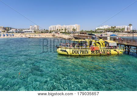 PROTARAS, CYPRUS - JUNE 16, 2016: Tourists on yellow dolphin submarine cruise boat, at the pier, sea shores and hotels
