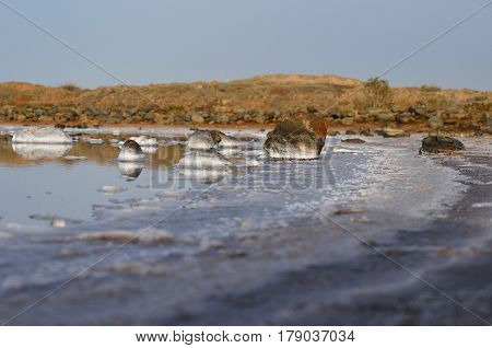 Saltwater lagoon with many stones in the shore
