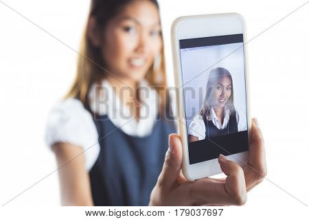 Smiling businesswoman taking a selfie on white background