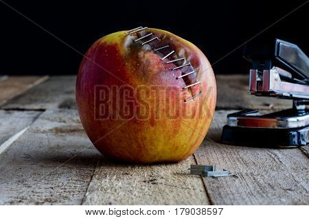 Apple stapled with a stapler on an wooden table