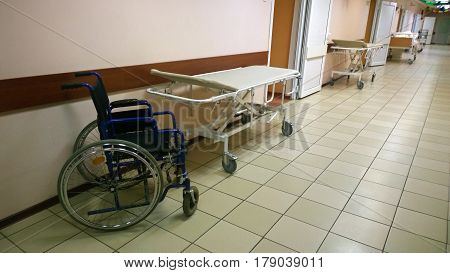 Bright, clean hallway in a medical facility - along the walls are medical bed and wheelchair