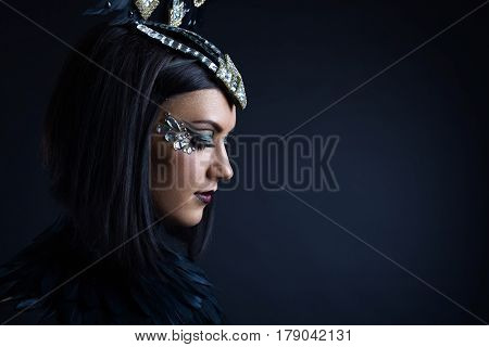 portrait of young beautiful woman in black with ornaments of rhinestone and feathers poster