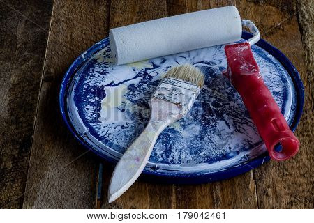 Paint brush and roller on a old table