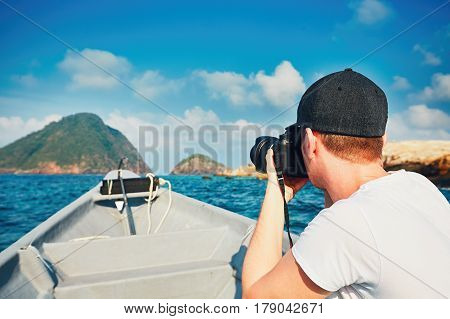 Young photographer with dslr camera shooting on the boat.
