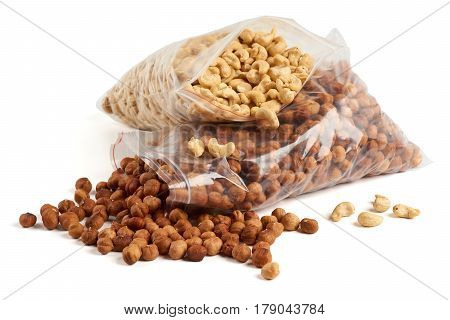 Cashew and hazelnuts in opened transparent zipper plastic bags over white