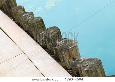 Diagonal line made by wooden logs to secure the pier