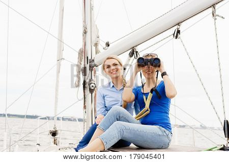 Two beautiful, attractive young girls with binocular on a yacht. Traveling, vacation, tourism, concept.
