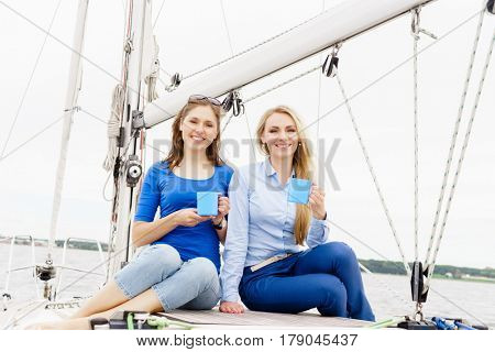 Two beautiful, attractive young girls drinking coffee on a yacht. Traveling, vacation, tourism, concept.