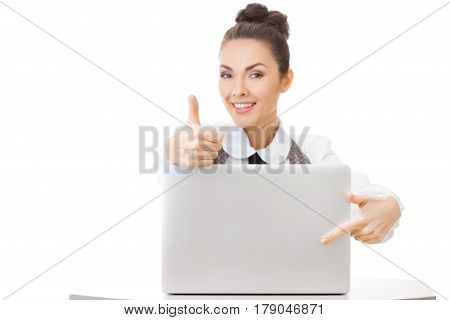 Cheerful office-worker showing thumbs up in front of laptop adn pointing to laptop screen blank sign. Smiling happy woman at work against white isolated background