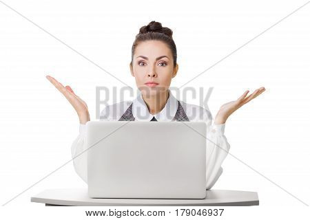 Confused businesswoman at work with laptop shrugging shoulders over white isolated background. Woman in question gesture looking at camera