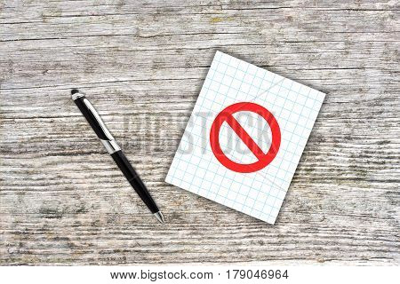 Red Prohibition Symbol On Checkered Paper Note With Pen. Wooden Background. Censorship Concept