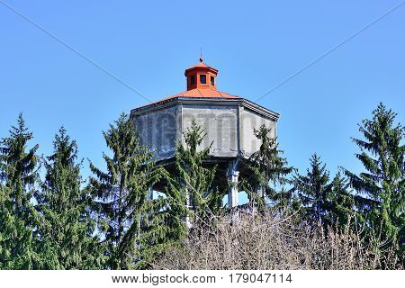 Old betone (concrete) water tower with painted roof against blue sky