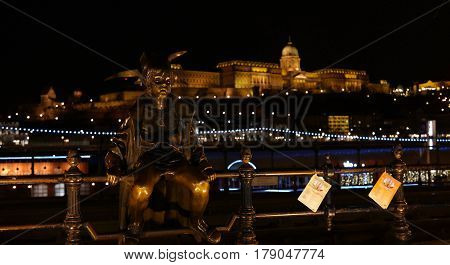 A night scene of the Little Princess statue by tram tracks next to Danube embankment with Buda castle in the background