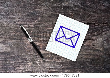 Blue Mail Symbol On Checkered Paper Note With Pen. Wooden Background