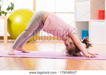 Child preschooler doing fitness exercises on rug at home