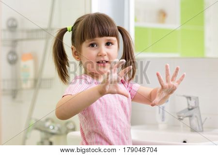child washing hands in bathroom and showing soapy palms
