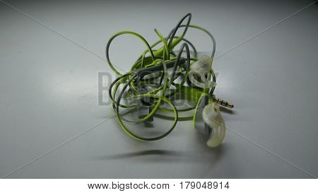 green color ear piece with a bundle of entangled cable